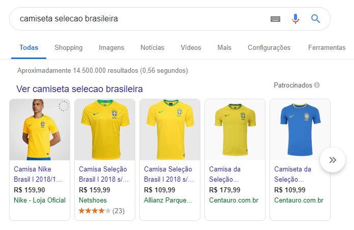"""A imagem mostra a pesquisa """"camiseta selecao brasileira"""" ao ser realizada no Google. Nos resultados, é possível visualizar diversos anúncios do Google Shopping apresentando o produto """"Camiseta da Seleção Brasileira""""."""