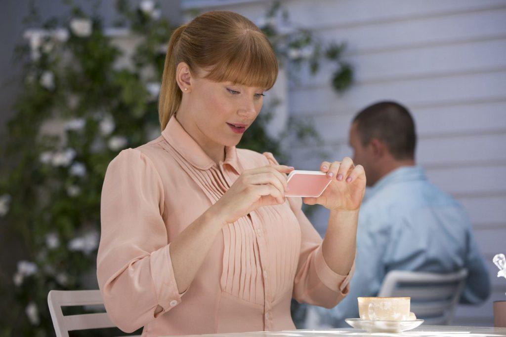 A imagem apresenta a personagem Lacie Pound, de Black Mirror, olhando para uma tela de celular.
